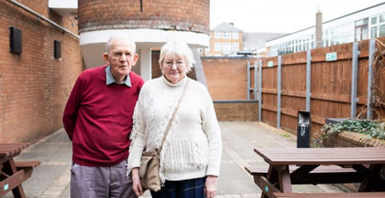 An elderly man and woman stand together