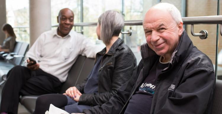 Three people sit in a waiting room. One man is holding a newspaper and smiling.