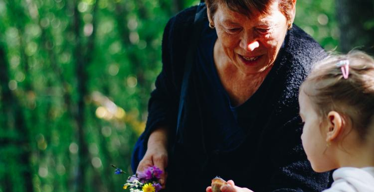An older women shows a young girl a shell and a flower outdoors