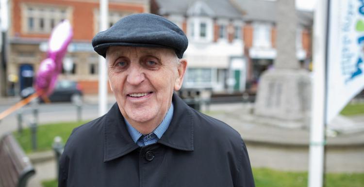 older man standing in street