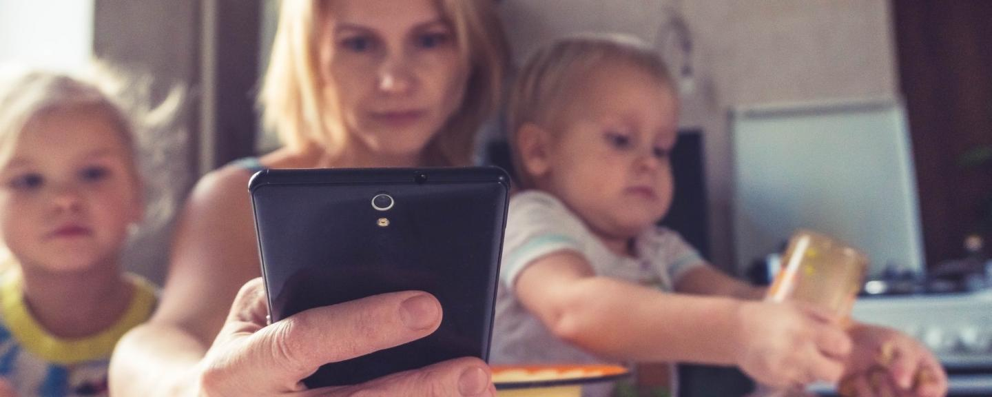 A mum looks at her phone surrounded by her young children