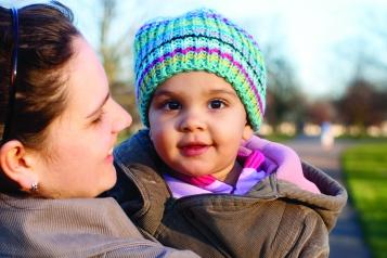 A baby in a knitted hat is held by her mum and looks at camera