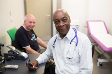 Image of a male doctor speaking to a male patient.