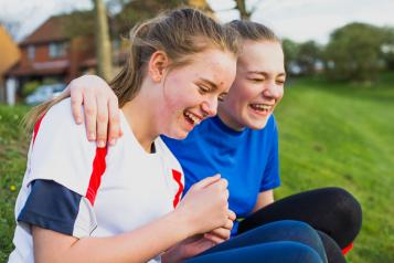 Two teenage girls sit on the grass laughing