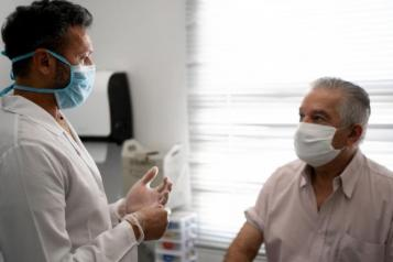 Male patient sitting on a bed talking to a male doctor. Both are wearing masks.