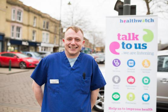Male nurse standing in front of a Healthwatch sign that says 'have your say'.