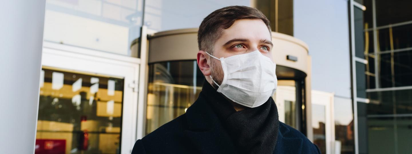 Man wearing a mask outside a building