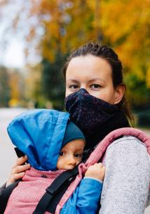 Mum wearing a mask carrying a baby in a sling